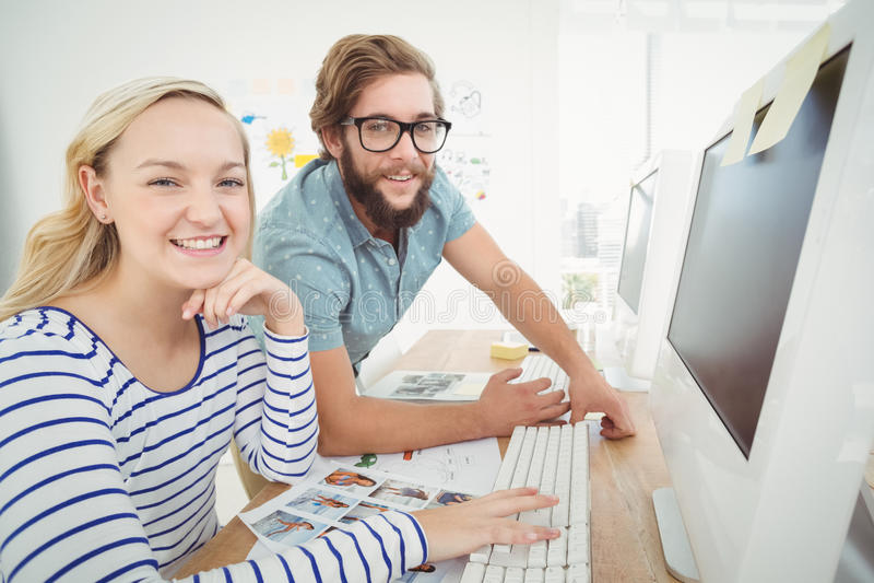 Porträt von glücklichen Geschäftsleuten am Computertisch stockbilder