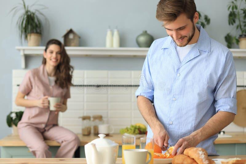 Porträt von glücklichen jungen Paaren in den Pyjamas, die zusammen morgens in der Küche, trinkender Orangensaft zu Hause kochen stockfotos