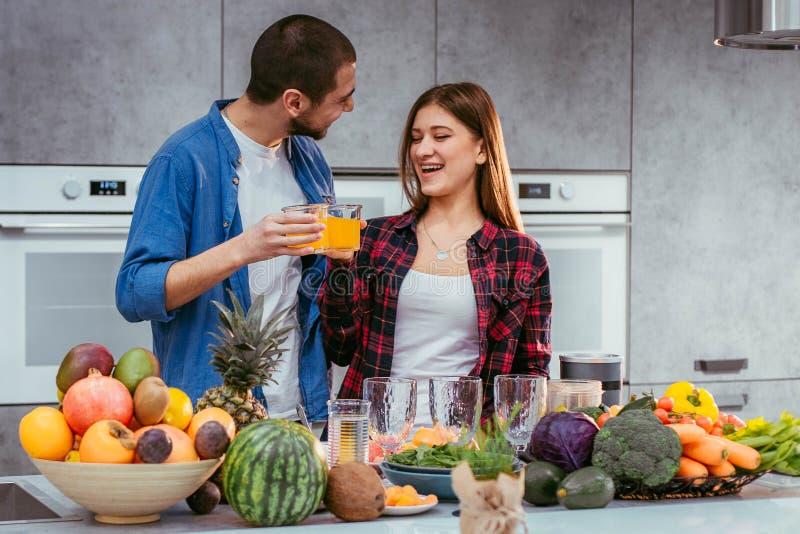 Porträt von glücklichen jungen Paaren in der Küche, die zusammen trinkenden Orangensaft morgens zu Hause kocht stockfoto