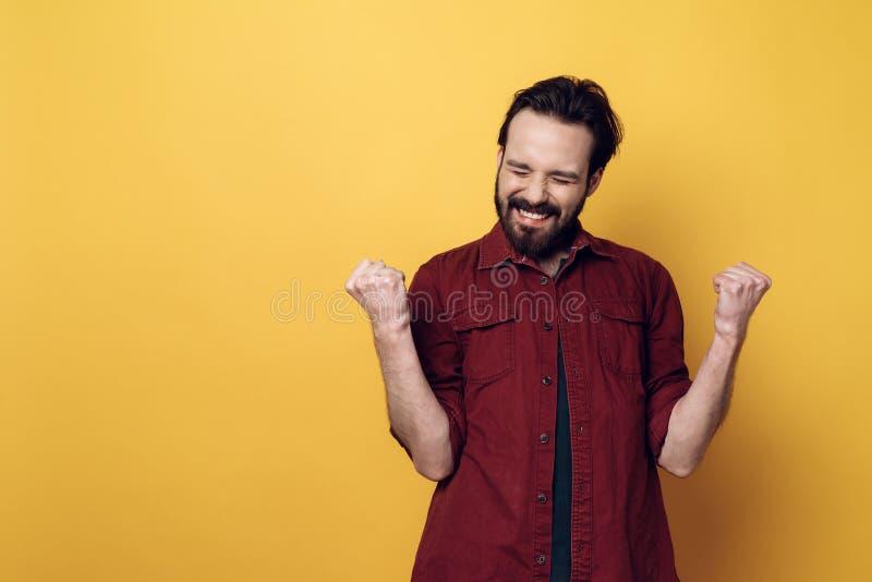 Porträt von glücklicher bärtiger Mann-zusammenpressenden Fäusten lizenzfreies stockbild