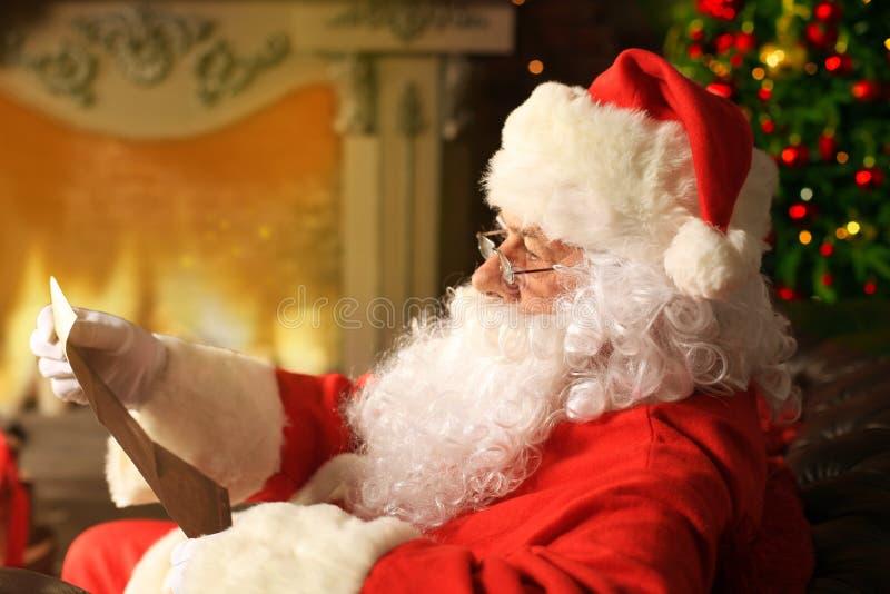Porträt von glücklicher Santa Claus zu Hause sitzend an seinem Raum nahe Weihnachtsbaum und Weihnachtsbrief oder Wunschliste lese stockbilder