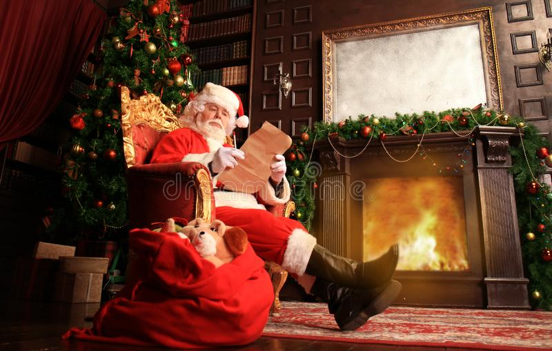 Porträt von glücklicher Santa Claus zu Hause sitzend an seinem Raum nahe Weihnachtsbaum und Weihnachtsbrief oder Wunschliste lese lizenzfreie stockfotos