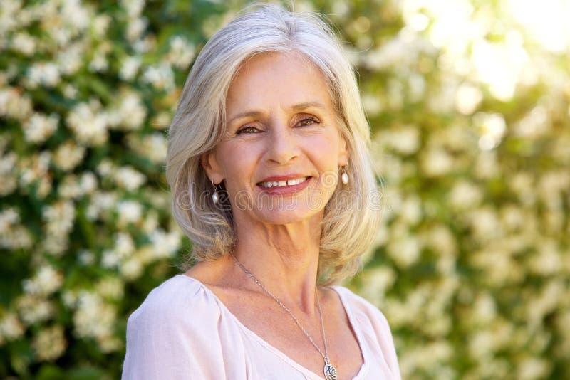 Porträt von glücklicher stehender Außenseite der älteren Frau im Sommer stockbilder