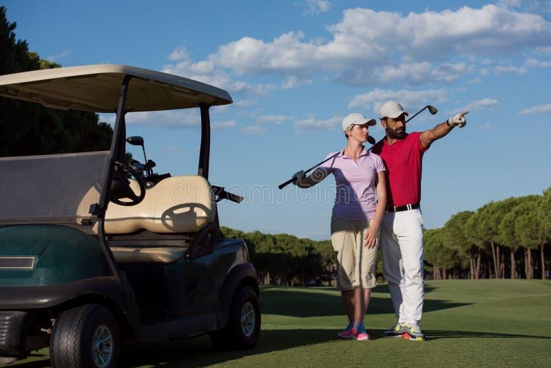 Porträt von Golfspielerpaaren auf Golfplatz lizenzfreie stockfotos