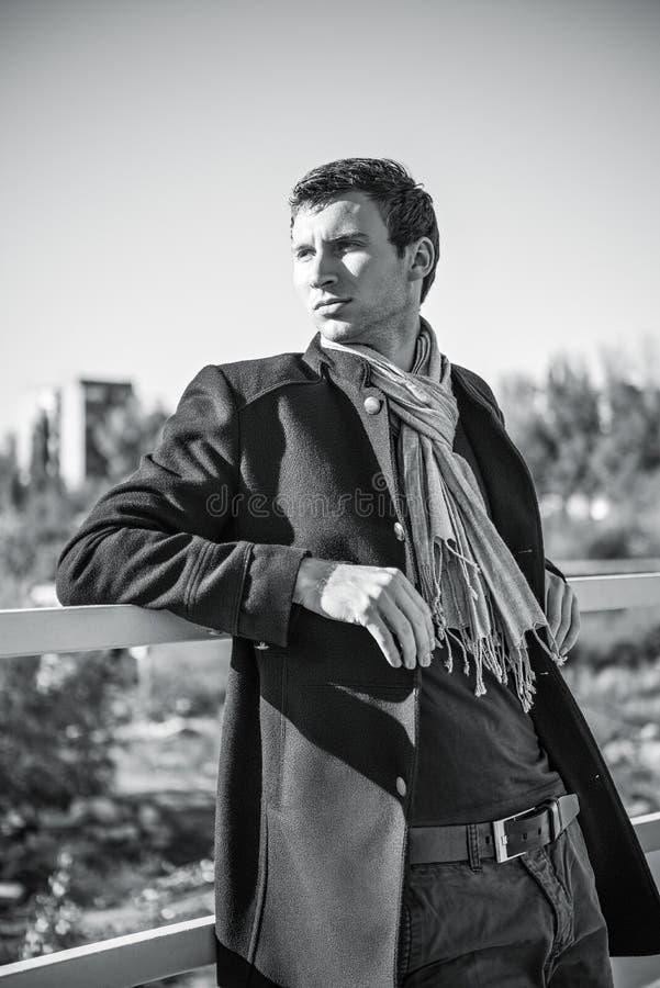 Porträt von hübschen tragenden Jeans, von Mantel und von Schal des jungen Mannes lizenzfreies stockbild
