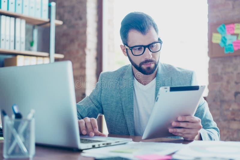 Porträt von jungem, ernst, IT-Fachmann, der Tablette in einer hält stockbilder