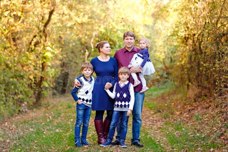 Porträt von jungen Eltern mit drei Kindern Mutter, Vater, zwei Kinderbruderjungen und wenig nette Kleinkindschwester stockbild