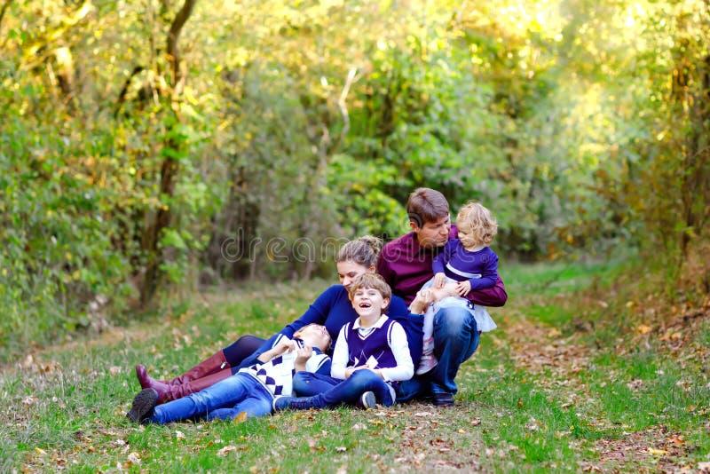 Porträt von jungen Eltern mit drei Kindern Mutter, Vater, zwei Kinderbruderjungen und wenig nette Kleinkindschwester stockfotografie