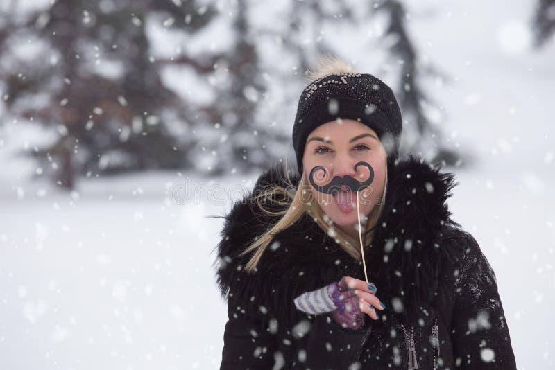 Porträt von jungen Frauen mit Schnurrbartpapierstützen am schneebedeckten Tag stockbilder
