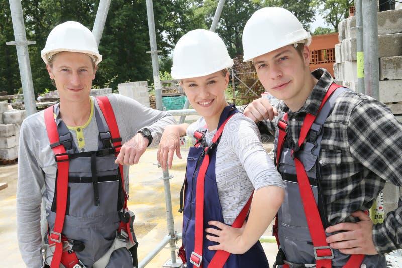 Porträt von jungen Leuten mit Sturzhelmen im Bau lizenzfreie stockfotos