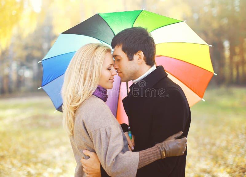 Porträt von jungen liebevollen Paaren mit dem bunten Regenschirm, der Herbst umarmt stockbilder
