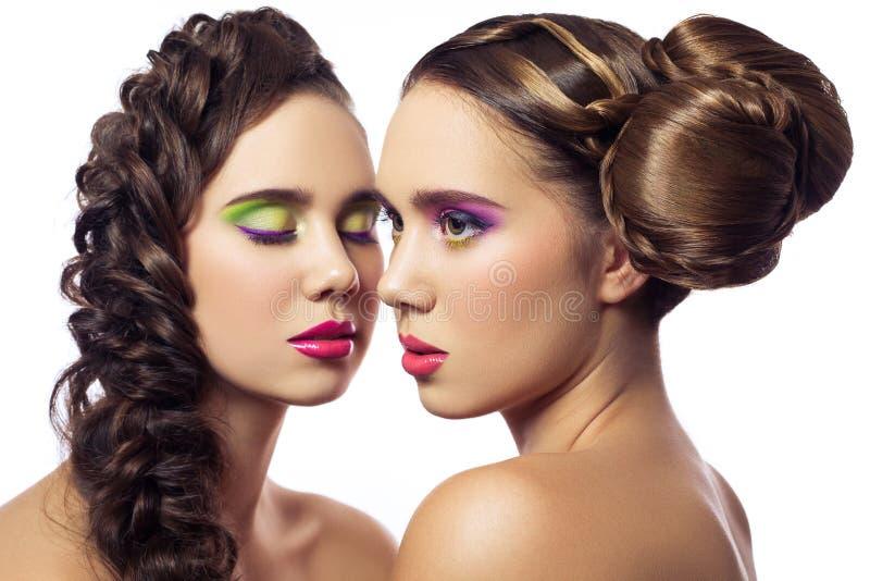 Porträt von jungen Modefrauen der schönen Zwillinge mit Frisur und rotem rosa grünem Make-up Getrennt auf weißem Hintergrund stockbild
