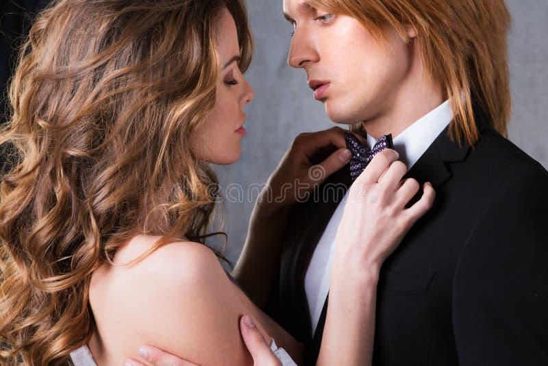 Porträt von jungen Paaren in der Liebe, die am Studio aufwirft, kleidete in der klassischen Kleidung an stockbild