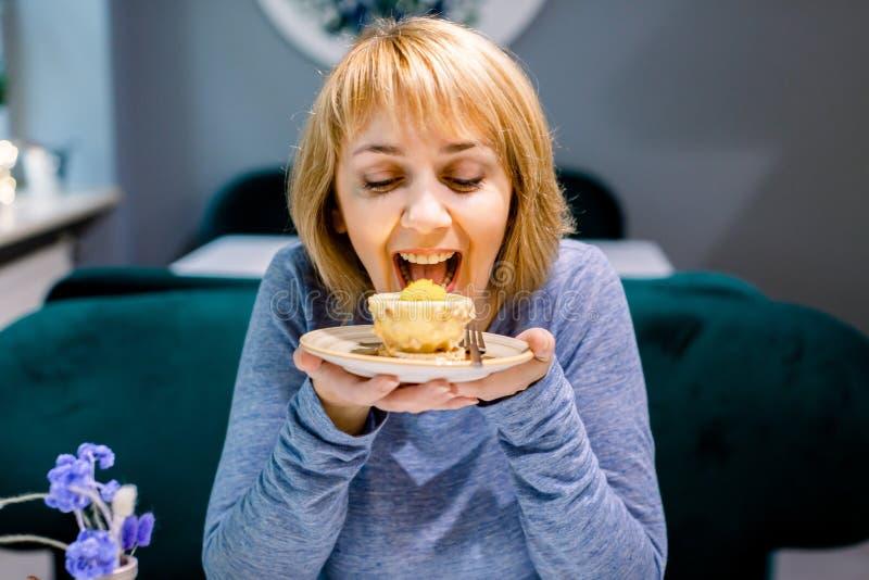 Porträt von jungen, ziemlich lächelnden Frauen, die Kuchen mit großem Vergnügen im Café essen Leckeres Dessert im Café Frauenvere stockfoto