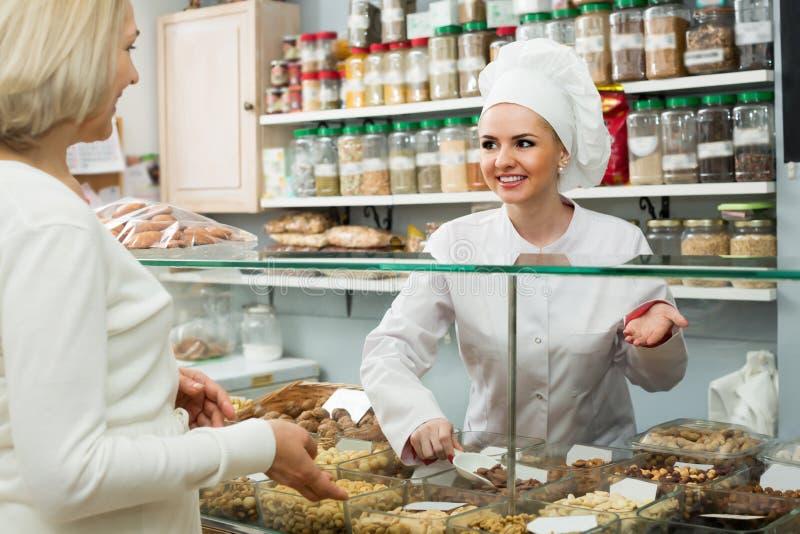Porträt von kaufenden Nüssen des Verkäufers und des Kunden lizenzfreie stockfotografie