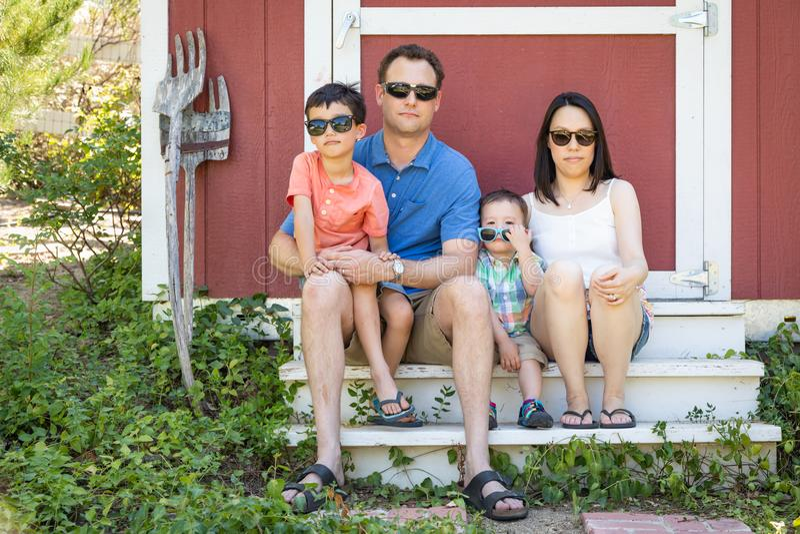 Porträt von kaukasischen und chinesischen Paaren mit Mischrasse-Söhnen lizenzfreie stockfotos