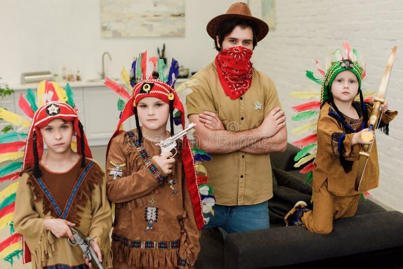 Porträt von kleinen Jungen in den einheimischen Kostümen und im Vater im Hut und von rotem Bandana, der Kamera betrachtet lizenzfreies stockbild