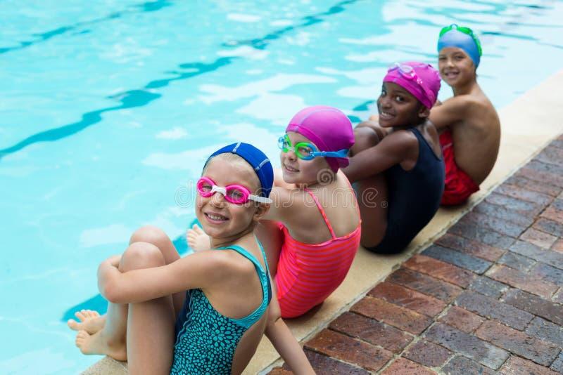 Porträt von kleinen Schwimmern am Poolside stockfoto
