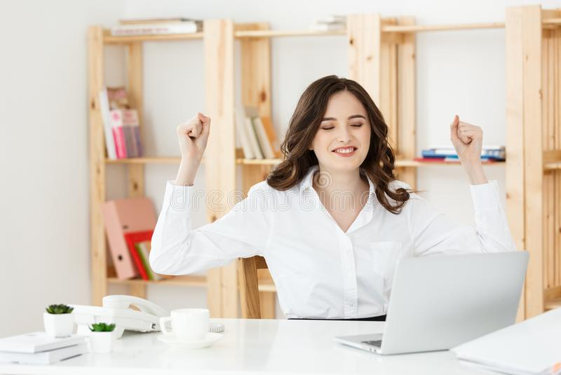 Porträt von lächeln recht junge Geschäftsfrau, die auf Arbeitsplatz sitzt stockfotografie