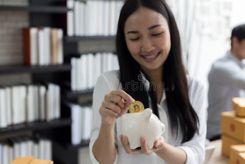 Porträt von lächelndem asiatischem Sparschwein und Münze Griff der jungen Frau stockfoto