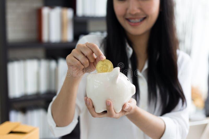 Porträt von lächelndem asiatischem Sparschwein und Münze Griff der jungen Frau lizenzfreie stockbilder