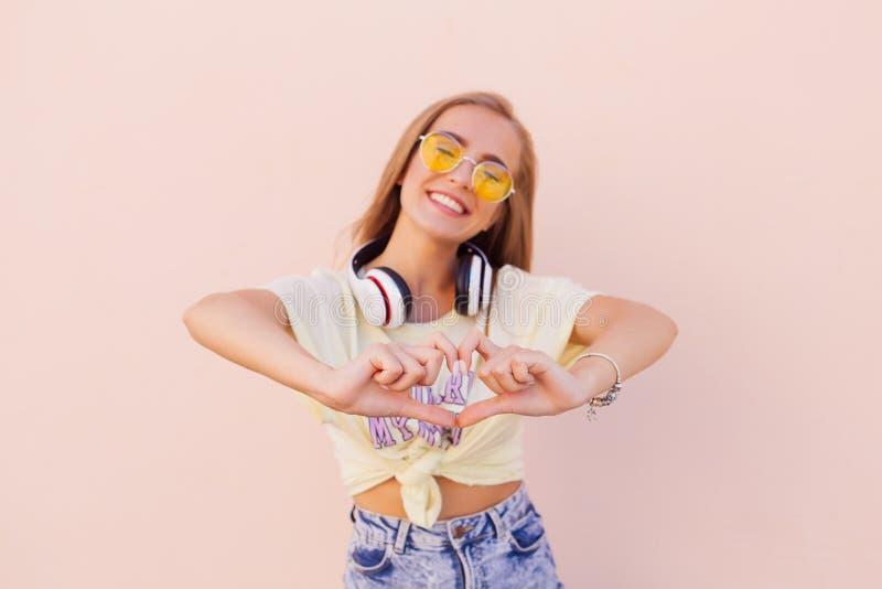 Porträt von lächelnden jungen Frauen der Schönheitsmode mit gelber Sonnenbrille, drahtlose Kopfhörer, Herz durch die Hände machen lizenzfreies stockbild