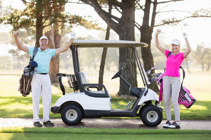 Porträt von lächelnden reifen Golfspielerpaaren mit den Armen angehoben stockfoto