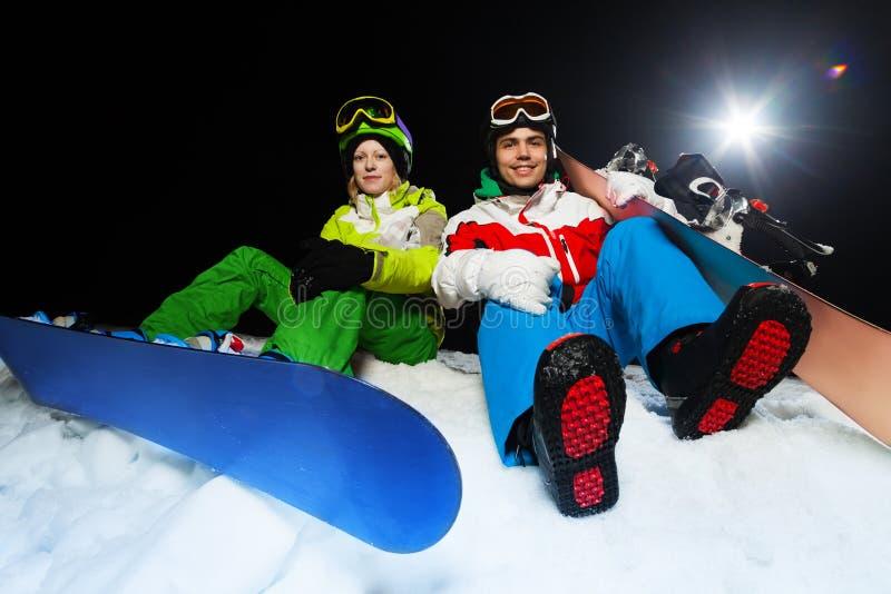 Porträt von lächelnden Snowboardern nachts stockfotografie