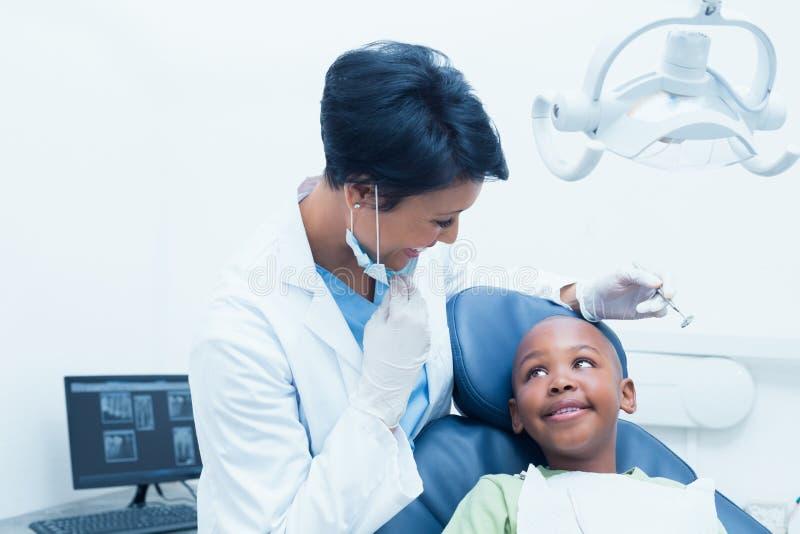Porträt von lächelnden Untersuchungsjungenzähnen des weiblichen Zahnarztes lizenzfreie stockbilder