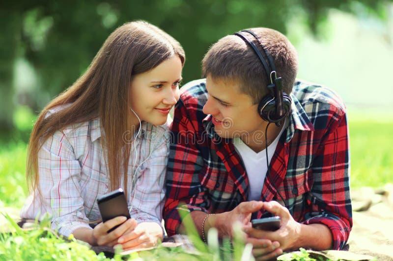 Porträt von Lügenauf dem Gras zusammen sich entspannen der jungen Paare stockfotografie