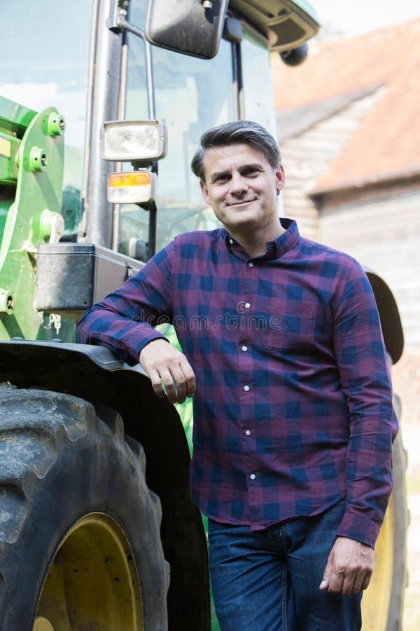 Porträt von Landwirt-Standing Next To-Traktor stockfotografie
