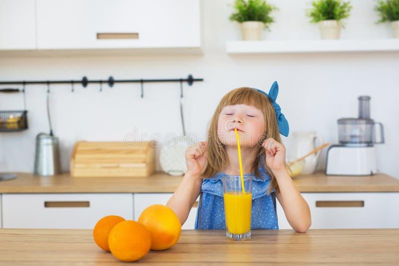 Porträt von lustigen Getränken eines kleinen Mädchens ein frischer Saft auf einer Tabelle stockfotografie