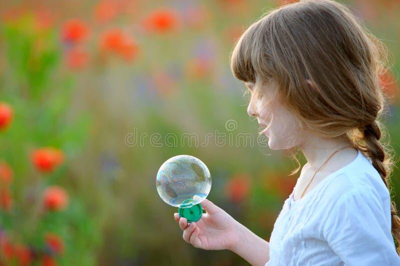 Porträt von lustigen reizenden Schlagseifenblasen des kleinen Mädchens lizenzfreie stockfotos