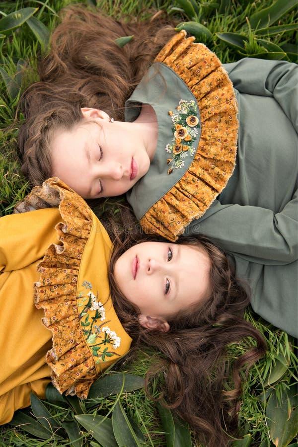Porträt von Mädchen in den Retro- Kleidern, die auf dem Gras eins umgedreht mit einem nachdenklichen Blick der Freude und der Ver stockbild