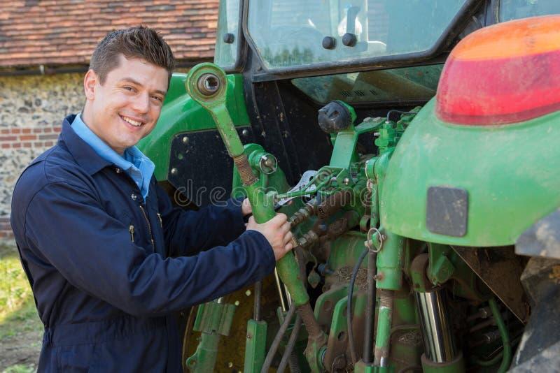 Porträt von Mechaniker-Repairing Tractor On-Bauernhof lizenzfreies stockfoto