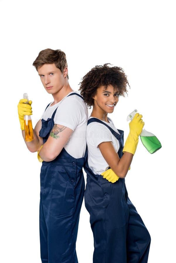 Porträt von multiethnischen Reinigern in den Gummihandschuhen mit Reinigungsmitteln in den Händen lizenzfreies stockbild