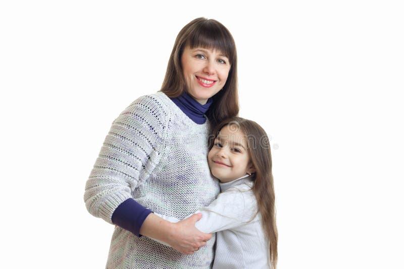 Porträt von nette Mütter und Töchter, die im Studio stehen und umarmen, lokalisierte auf einem weißen Hintergrund stockfoto