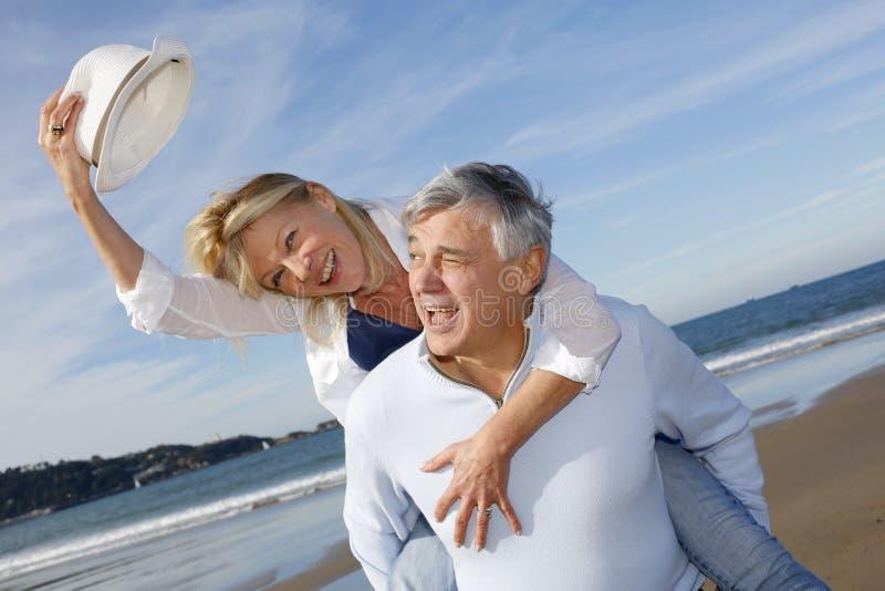 Porträt von netten älteren Paaren auf dem Strand, der Spaß hat stockbild