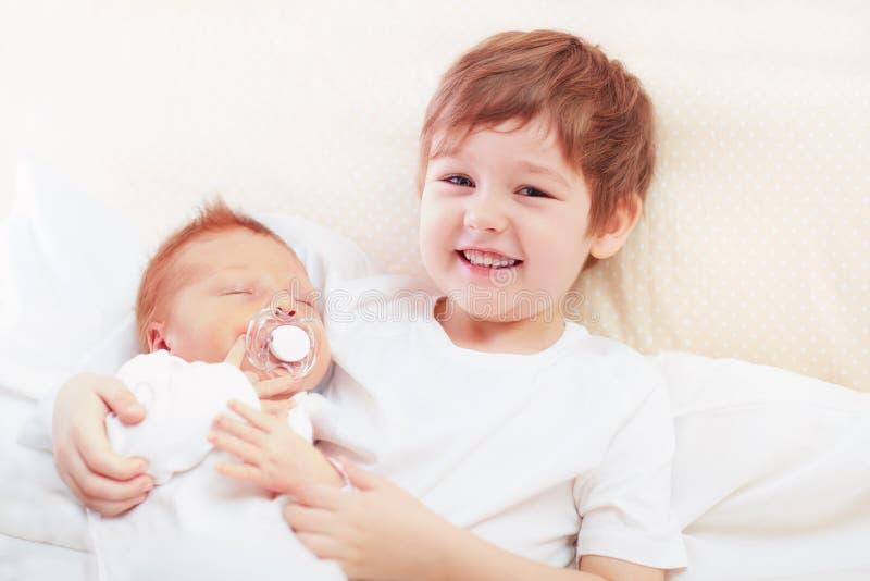 Porträt von netten glücklichen Geschwister Junge, der seinen Säuglingsbruder hält stockbild