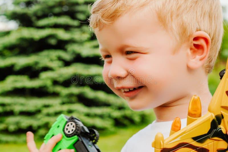 Porträt von netten glücklichen kleinen blonden Jungenholdingflächen- und -autospielwaren Entzückendes Kind, das in Park am sonnig stockbild