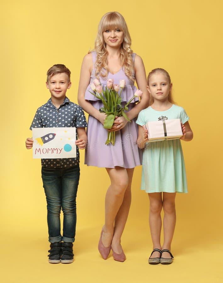 Porträt von netten Kleinkindern und von ihrer Mutter mit Geschenken auf Farbhintergrund stockfotos