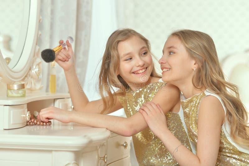 Porträt von netten Schwestern in den goldenen Kleidern, die nahe Frisierkommode sitzen stockbild