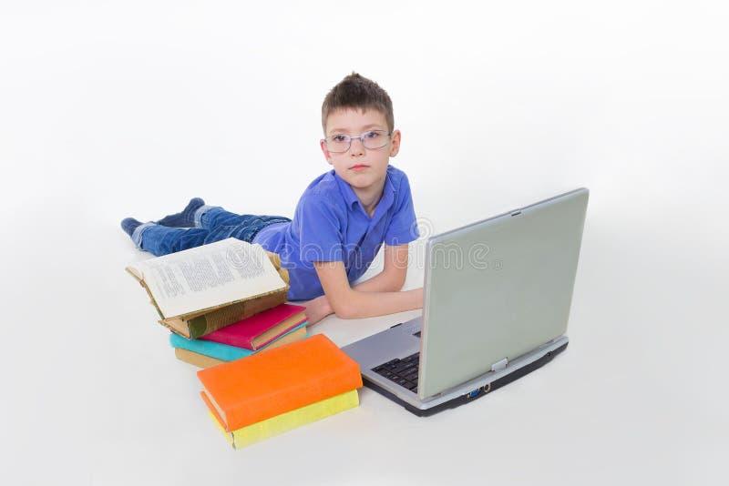 Porträt von netter Schüler Lügenwiyh Büchern und Schreiben auf Laptoptastatur stockfotos