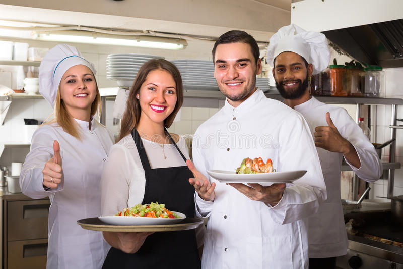 Porträt von positiven Küchenarbeitskräften stockbilder