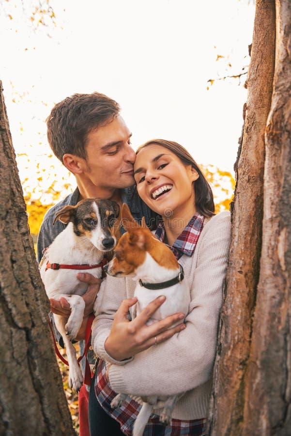 Porträt von romantischen jungen Paaren mit Hunden draußen lizenzfreies stockfoto