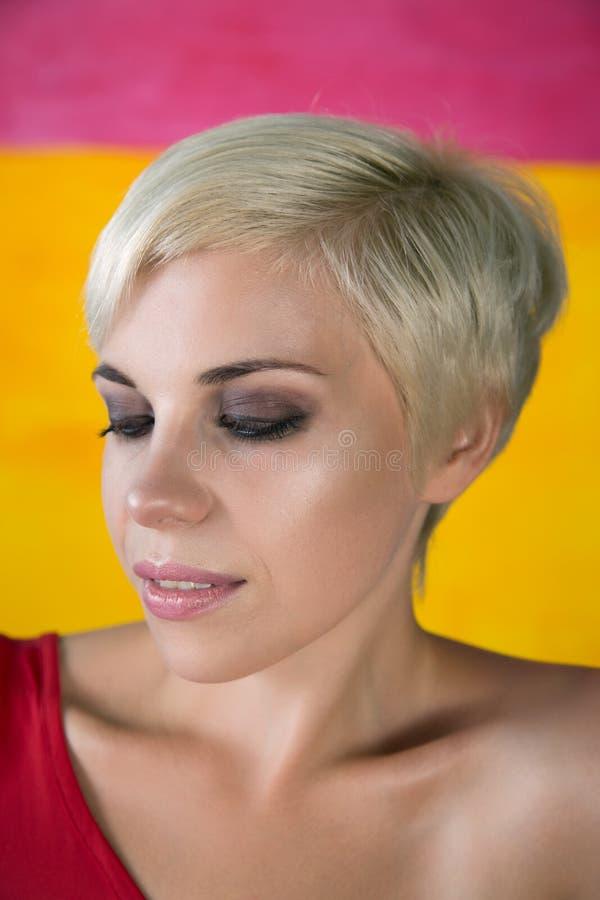 Porträt von schönen Blondinen im roten Kleid lizenzfreies stockbild