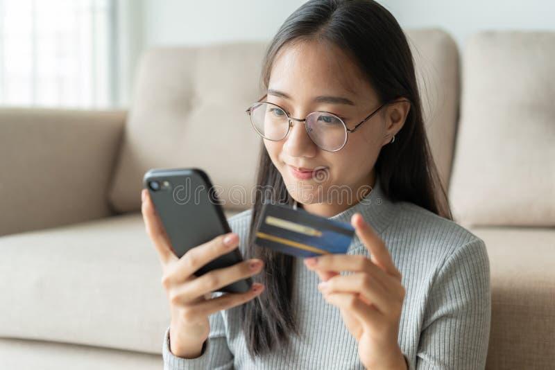 Porträt von schönen jungen Asiatinnen kaufen online mit einer Kreditkarte Asien-Mädchen benutzen Smartphone und machen online lizenzfreies stockfoto