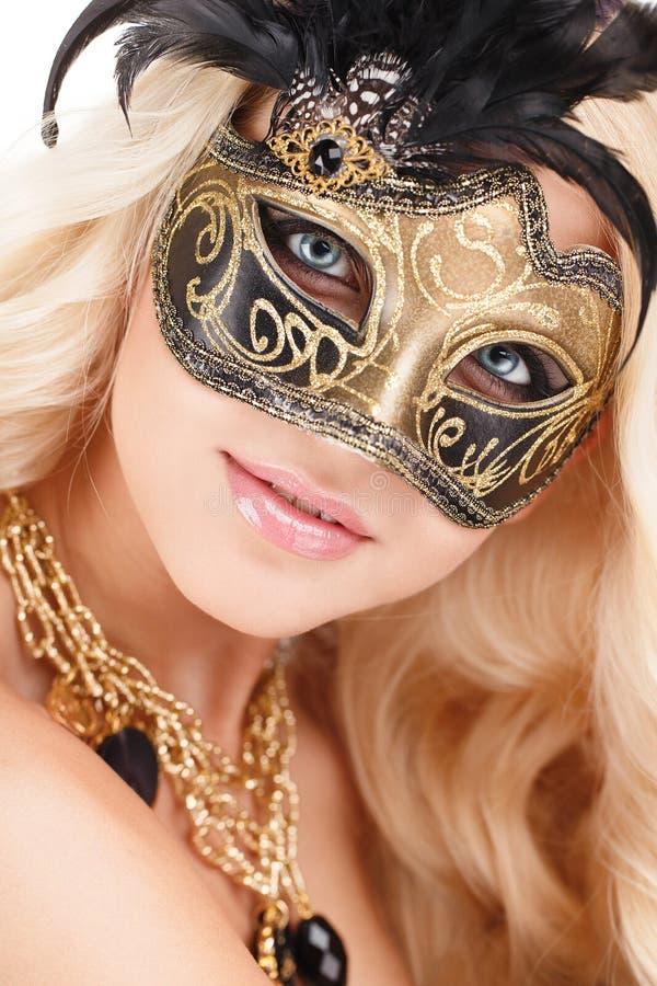 Porträt von schönen jungen Blondinen im Schwarzen und in der Goldmysteriösen venetianischen Maske. Modefoto auf weißem Hintergrund lizenzfreies stockbild