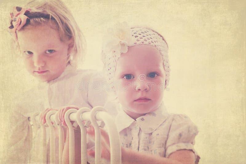Porträt von schönen kleinen Mädchen (Schwestern) in der Weinleseart lizenzfreie stockfotos