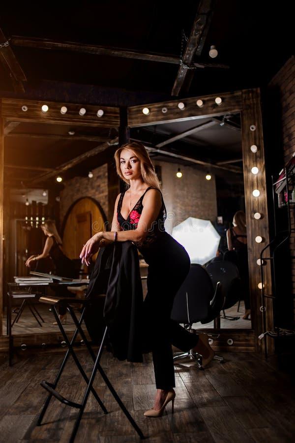 Porträt von schönen sexy jungen Blondinen in den schwarzen Hosen und in der Spitzewäsche im Dachboden lizenzfreie stockfotografie
